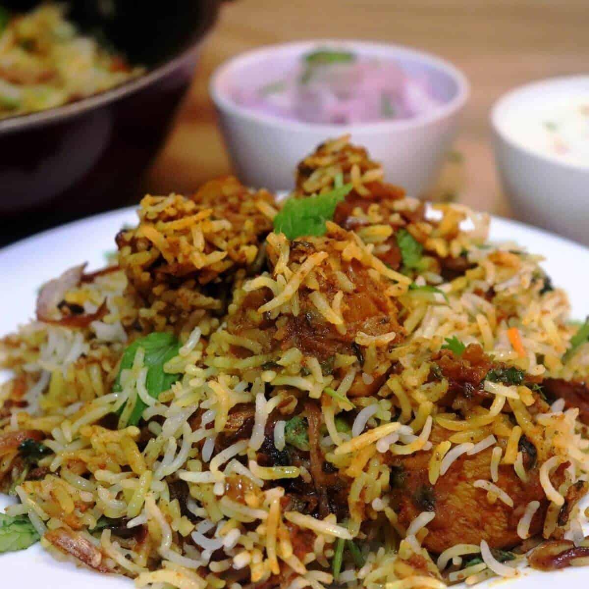 hyderabadi chicken dum biryani served on a white plate with raita & salad.