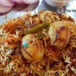 close-up of egg biryani served in a plate with raita and sliced onions
