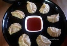 Veg momos served in a plate with spicy tomato sauce.