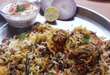 Hyderabadi biryani served with raita and onion slices.