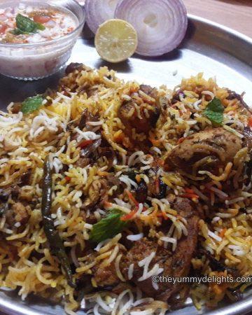 Hyderabadi biryani served with raita and onion slices.