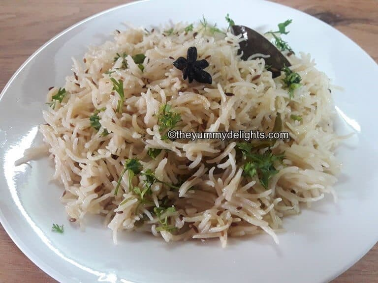 Jeera rice served in a white plate.