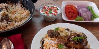 lucknowi chicken biryani served in a white plate with salad & raita.