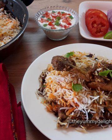 lucknowi chicken biryani served in a white plate with salad & raita.