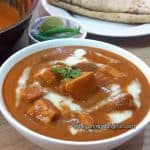 close up of paneer butter masala served with Roti & salad.