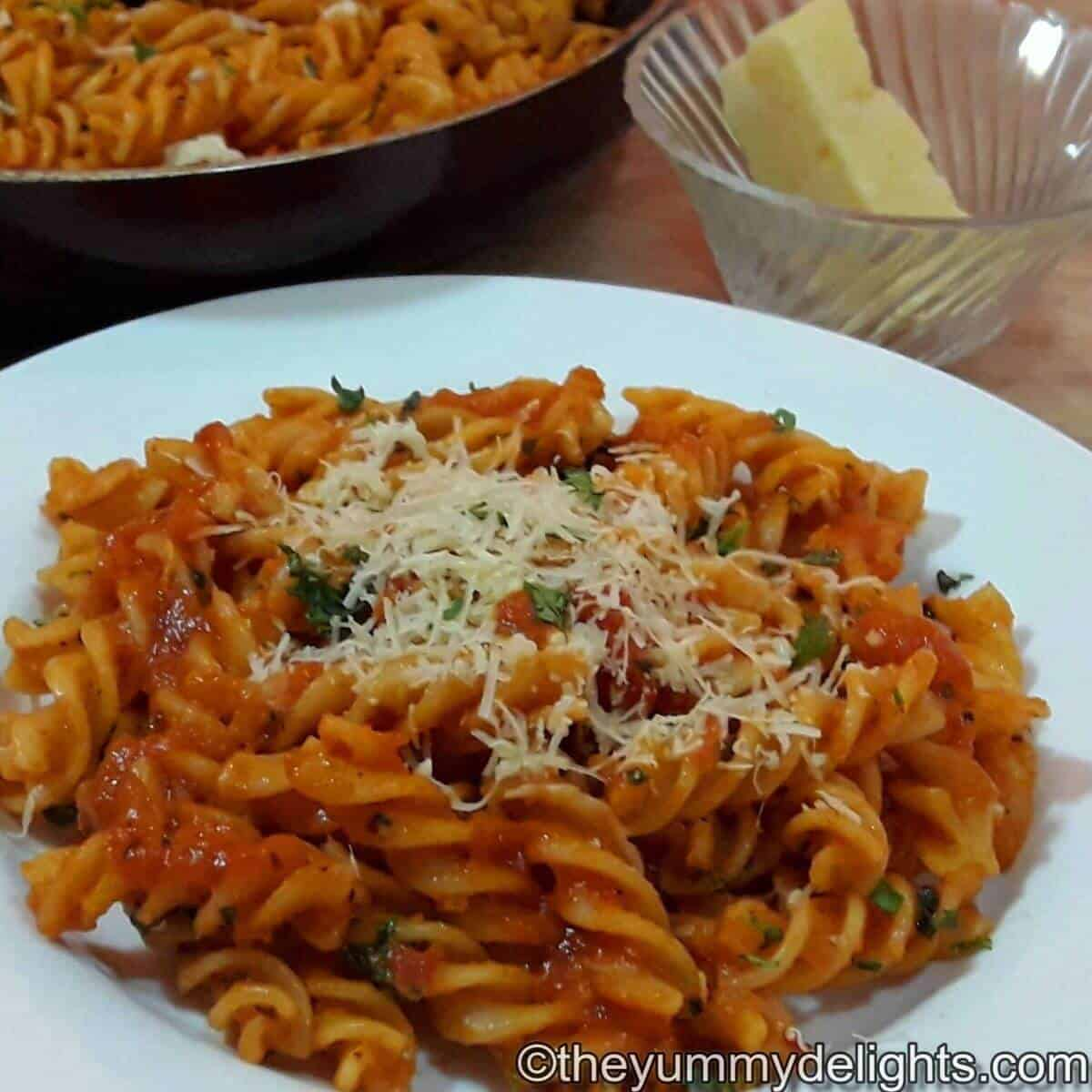 tomato pasta served in a white bowl.
