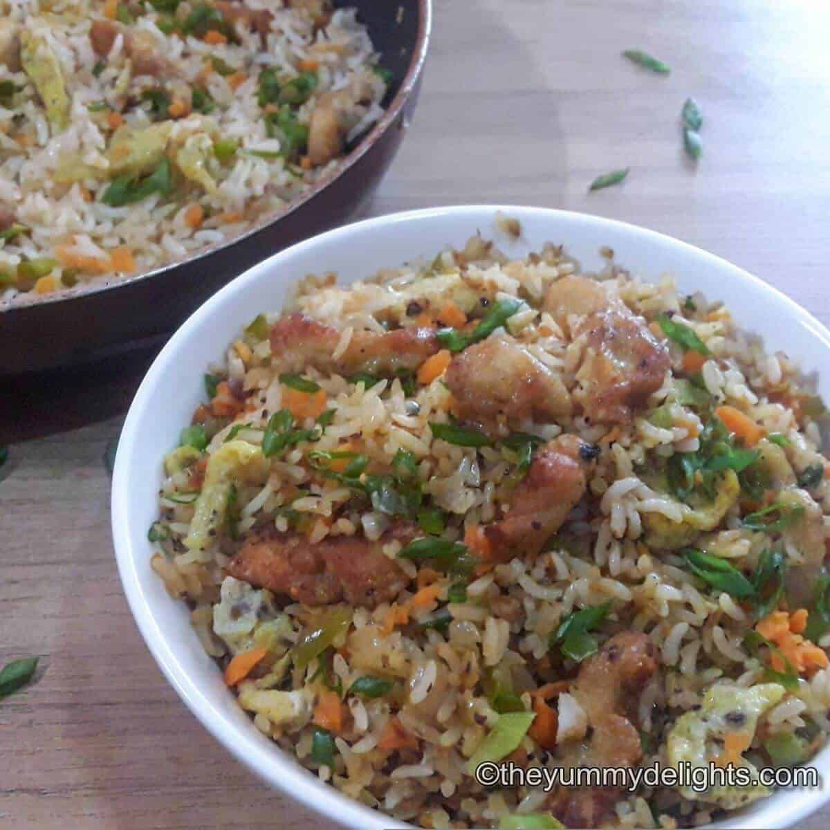 Chinese chicken fried rice served in a white bowl. Garnished with some spring onion greens.