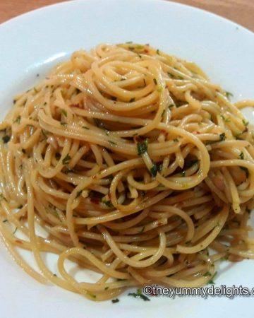 spaghetti aglio, olio e peperoncino served in a white plate.