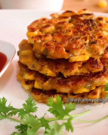 Corn fritters stacked & served in a white plate. Served with tomato sauce. Garnished with coriander leaf.