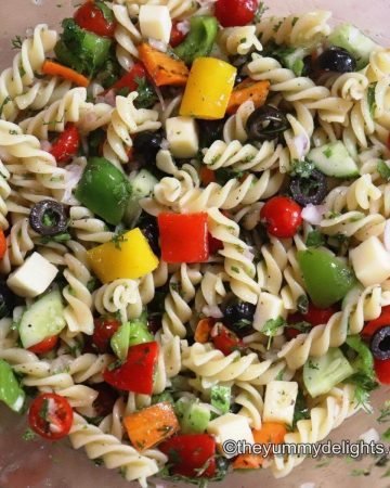 pasta salad with colorful vegetables in a mixing bowl.