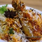 butter chicken biryani served in a white plate. Garnished with a star anise & coriander leaves,