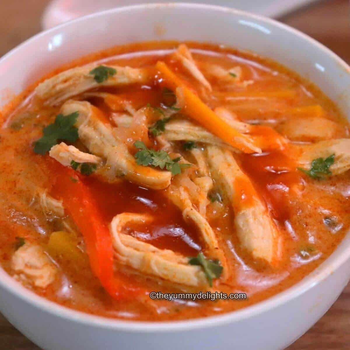 Thai chicken soup with rice noodles served in a white bowl. Garnished with cilantro & sriracha.