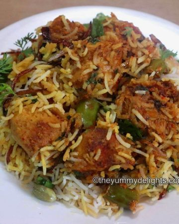 close-up image of chicken tikka biryani served in a white plate. Garnished with fried onions, mint and coriander leaves.