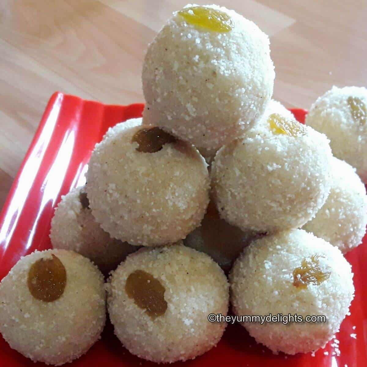 Maharashtrian style rava ladoo placed on a red plate. Garnished with raisins.