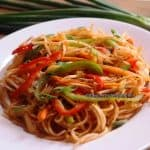 spaghetti marinara served in a white plate. Garnished with spring onion greens.