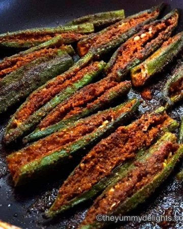 Bharwa bhindi with besan in a frying pan.