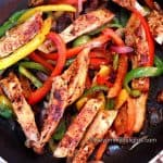 chicken fajitas in a black pan. You can see chicken strips, green bell pepper, red bell pepper, yellow bell pepper and onions.