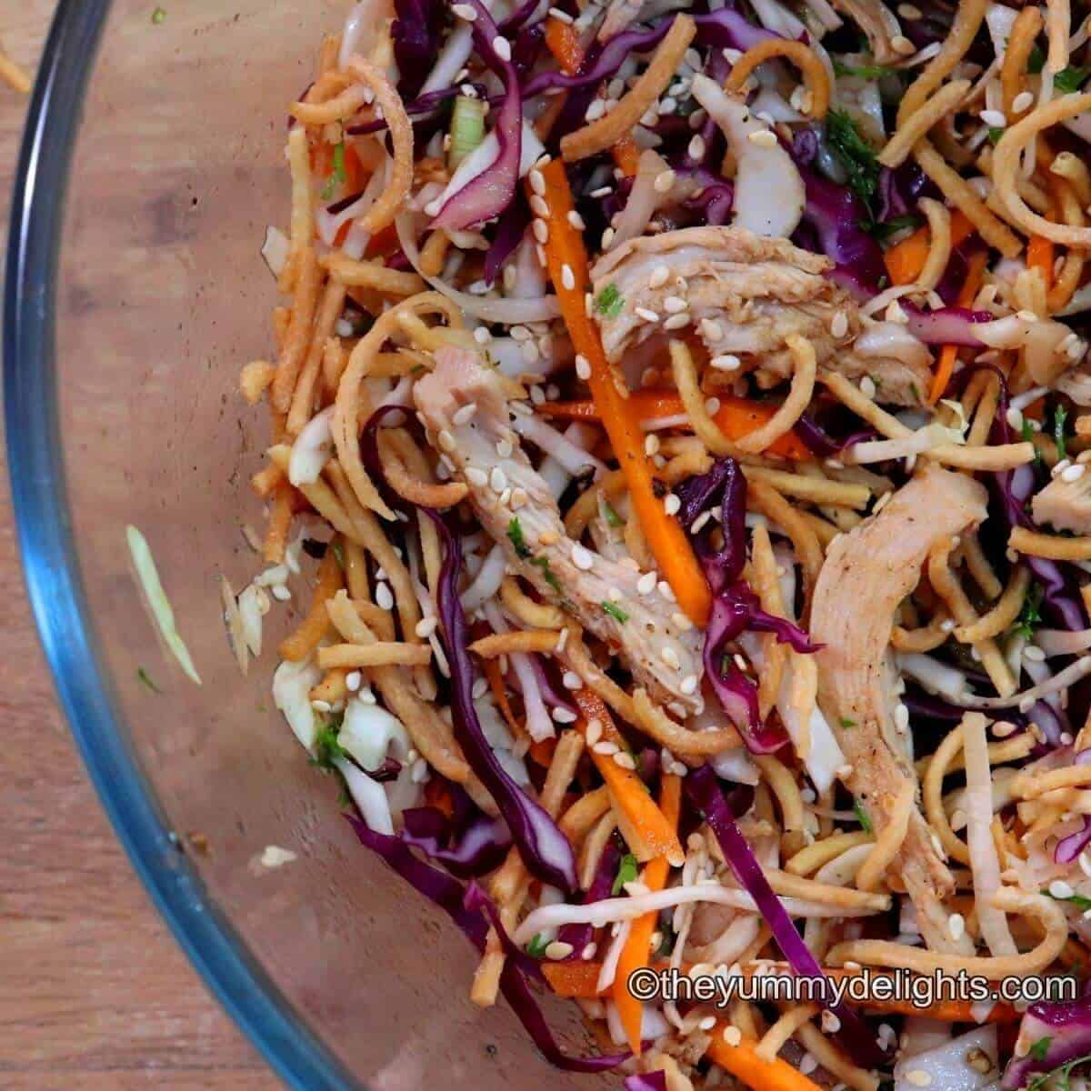 Side view of Chinese Chicken Salad in a glass bowl. Garnished with fried noodles and roasted sesame seeds.