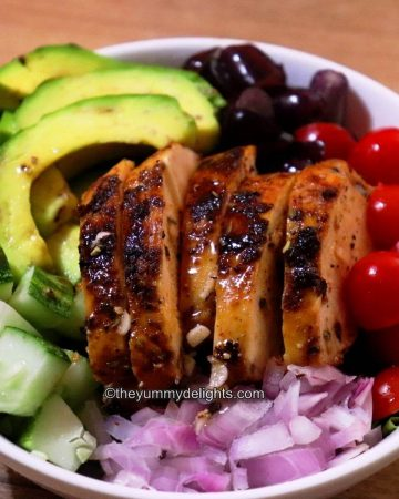 summer grilled chicken salad served in a white bowl with fresh fruits and vegetables.