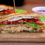 Close-up view of chicken club sandwich. The club sandwich is placed on a chopping board. THe layers of grilled chicken, tomato, cheese slice, lettuce leaves and fried eggs are visible.