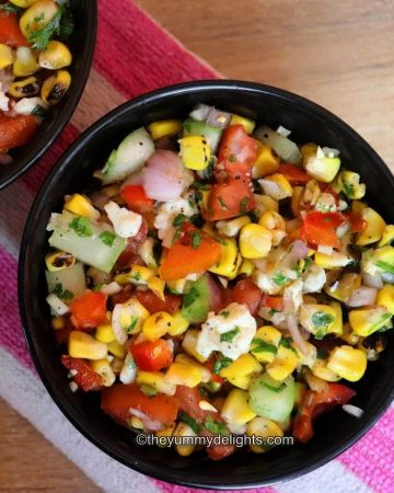 close-up of grilled corn salad in a black bowl. Another black bowl with corn salad is placed nearby.