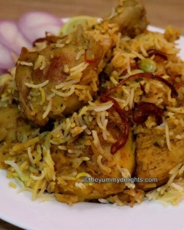 Kolkata chicken biryani served on a white plate with sliced onions and lemon wedge the side.