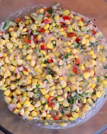 creamy corn salad in a glass bowl.