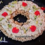Ghevar placed on a black color plate, topped with rabri and chopped nuts.