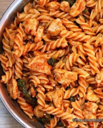 close-up image of tomato chicken spinach pasta in a skillet.