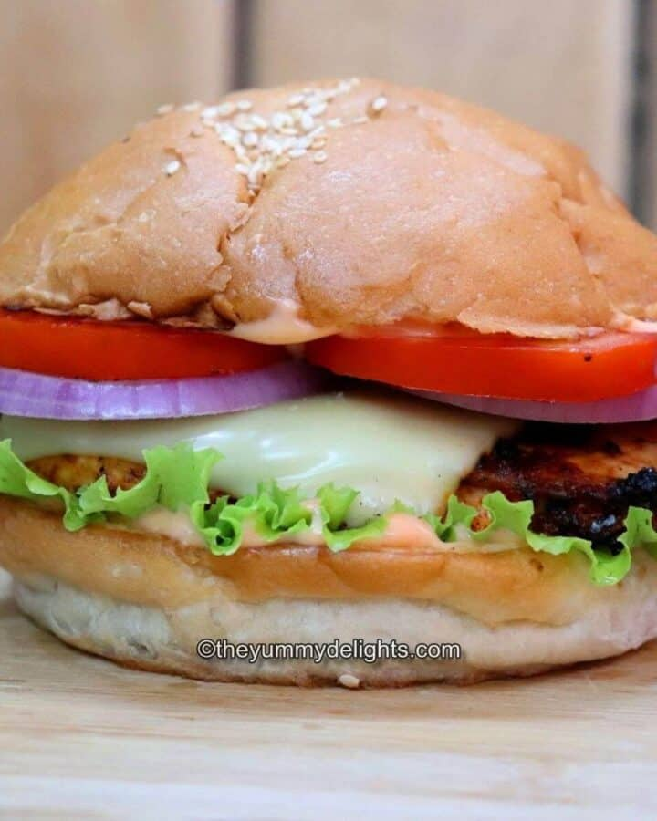 grilled cajun chicken sandwich placed on a chopping board. Side-view of the image.