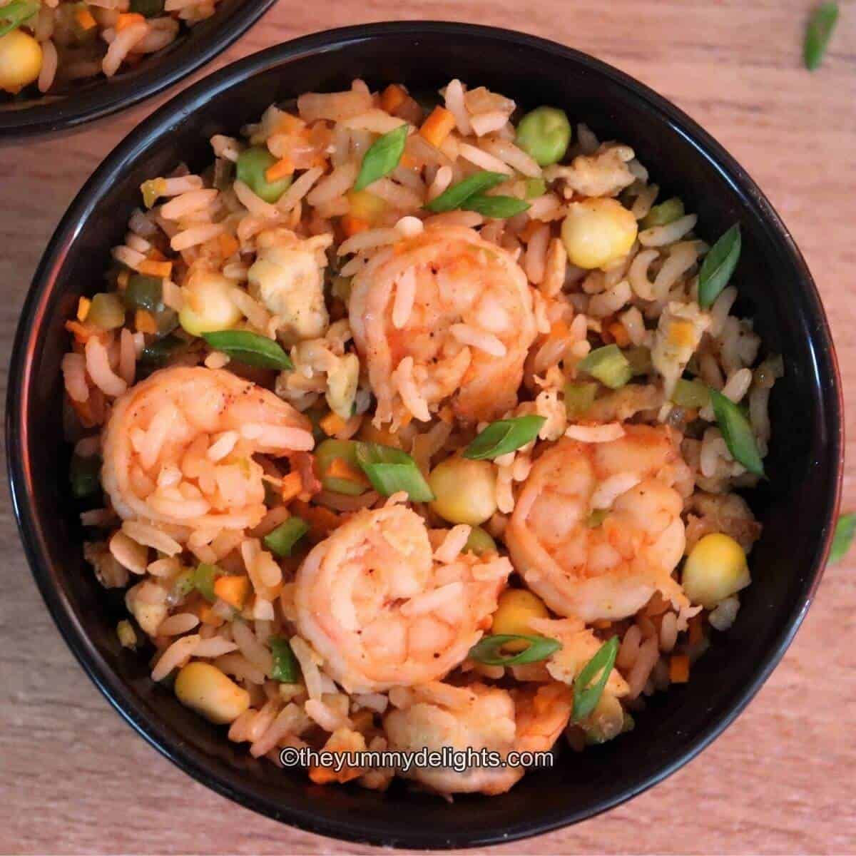 prawn fired rice served in a black bowl